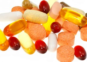 Pile of vitamin and mineral supplements, as well as fish oil capsules