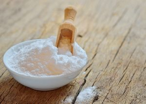 Bowl of baking soda with a wooden scoop