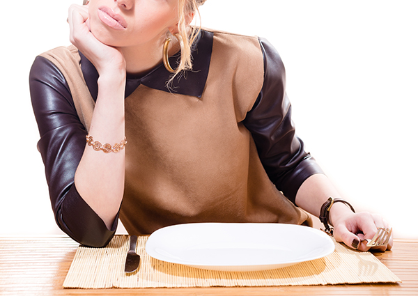 Woman sitting at a restaurant with an empty plate looking hungry