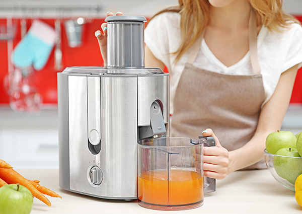 Woman making carrot juice in her kitchen with a juicer