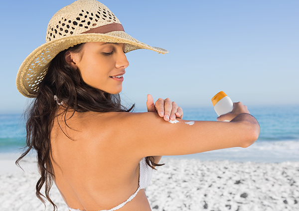 Woman at the beach applying sunscreen to her arm