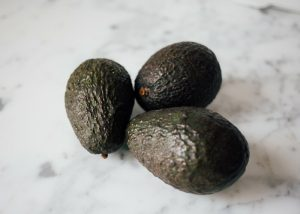 three ripe avocados on a marble cutting board