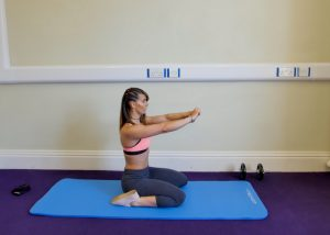 woman kneeling on an exercise mat doing butt exercises