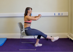 woman doing butt exercises sitting on a chair with one foot planted