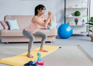 woman doing squats on an exercise mat in a room