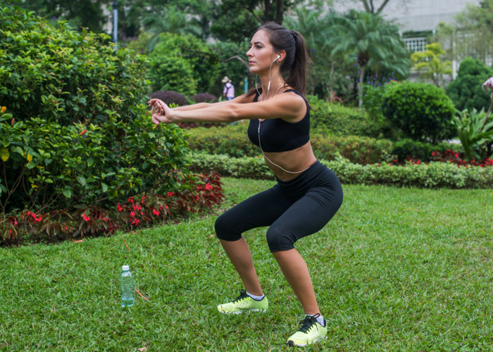 thin woman doing a butt exercises workout in park