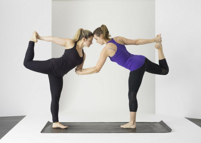 two women linking arms in a standing yoga pose