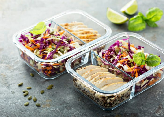 two meal prep containers filled with chicken and salad