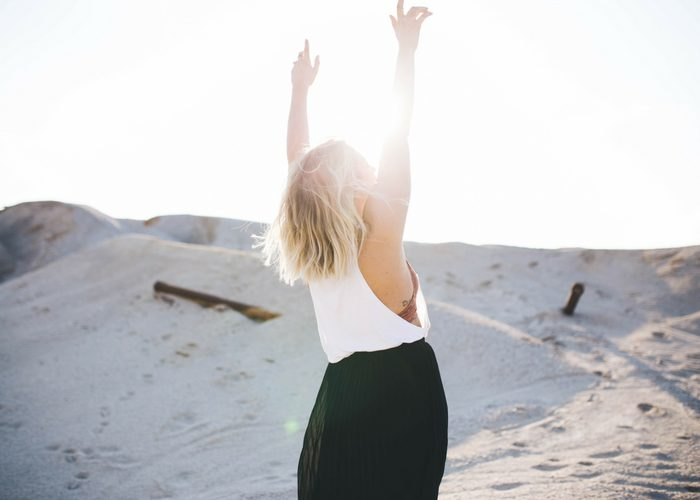 woman with raised arms back-lit by the sun
