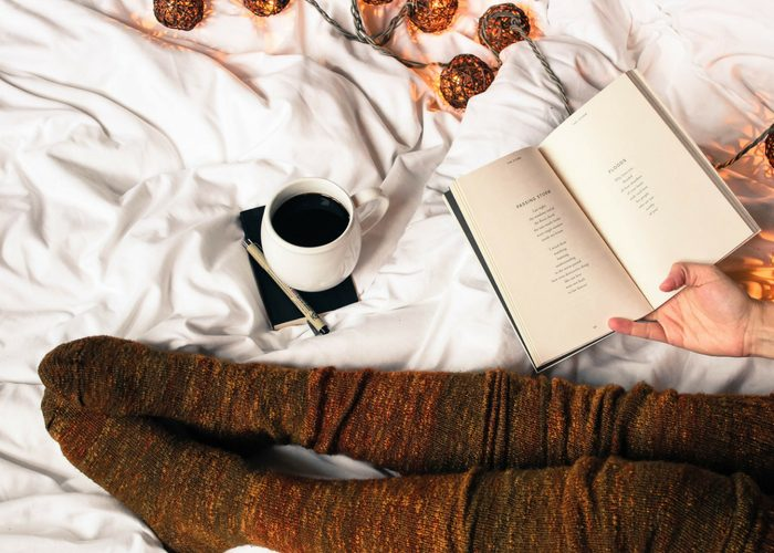 woman in bed holding a book of poetry