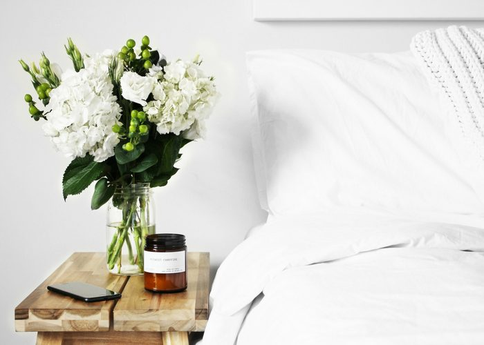 vase of white flowers next to a bed with white linens