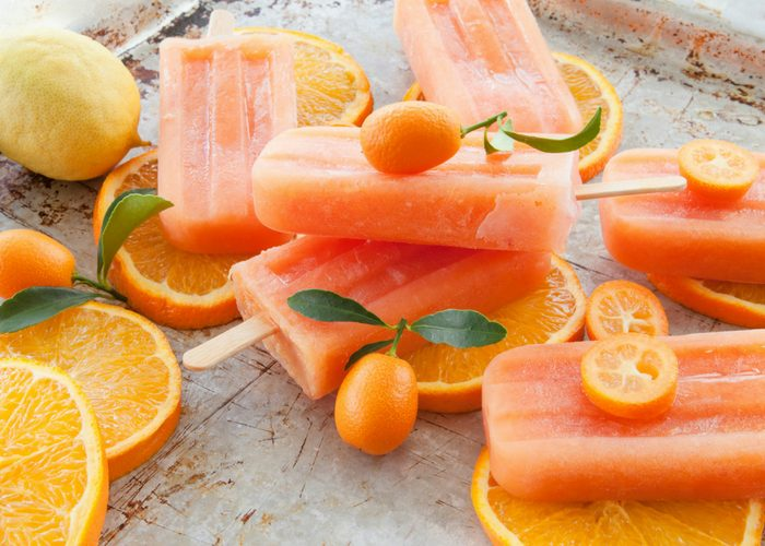 orange popsicles with orange slices on a metal tray