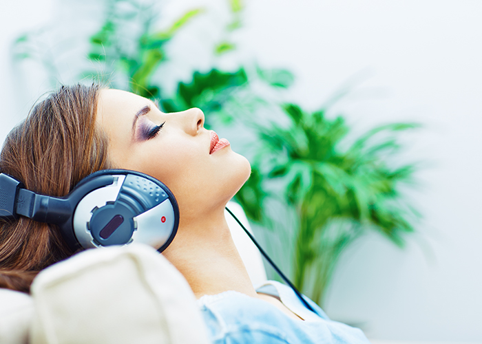 woman with eyes closed listening to music