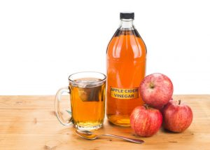 bottles of filtered apple cider vinegar with three red apples and a cup of tea