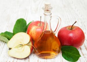 a bottle of apple cider vinegar with red apples
