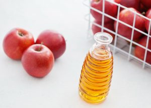 a bottle of apple cider vinegar with a basket of apples on a white background