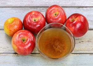 bowl of unfiltered apple cider vinegar including the mother and five red apples