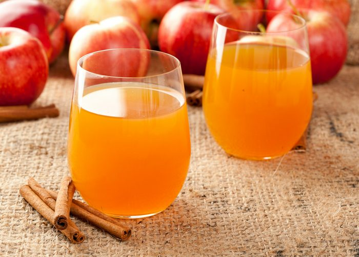 two glasses of apple cider vinegar drinks with red apples and cinnamon sticks