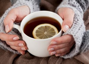 girl holding a mug of tea with a lemon slice in it