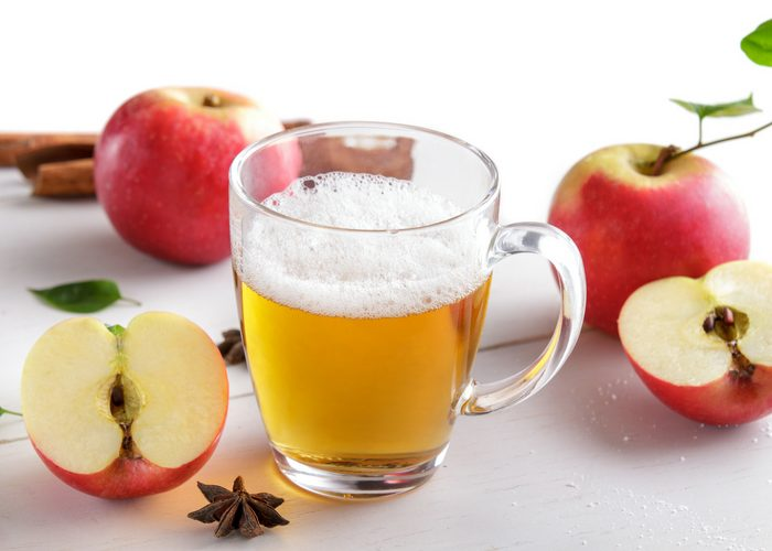 a frothy apple cider vinegar drink in a glass with red apples around it