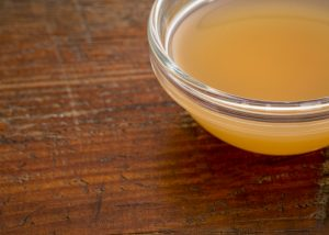 raw apple cider vinegar in a dish on a wooden table