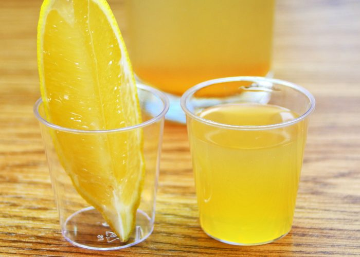 an apple cider vinegar drink recipe in a shot glass with lemon wedge