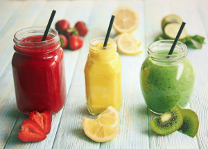 a strawberry, lemon, and kiwi smoothie in jars with straws