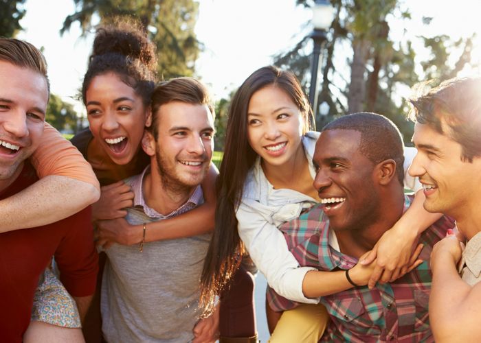 a group of friends smiling with their arms around each other
