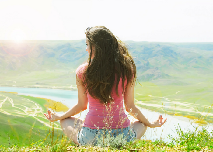 a woman peacefully meditating in a field looking out into a valley