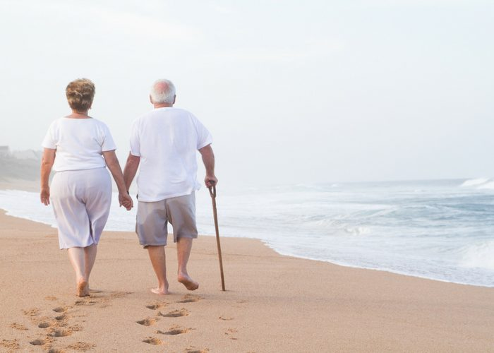 an elderly couple taking a walk along the beach holding hands