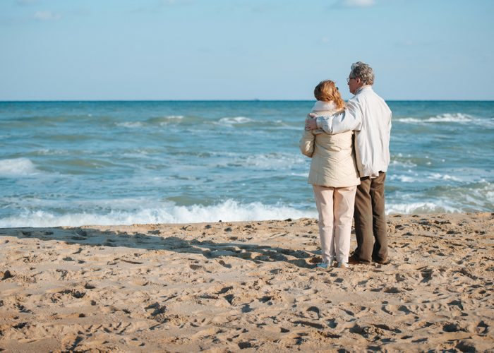 an old couple standing on a beach looking at the sea