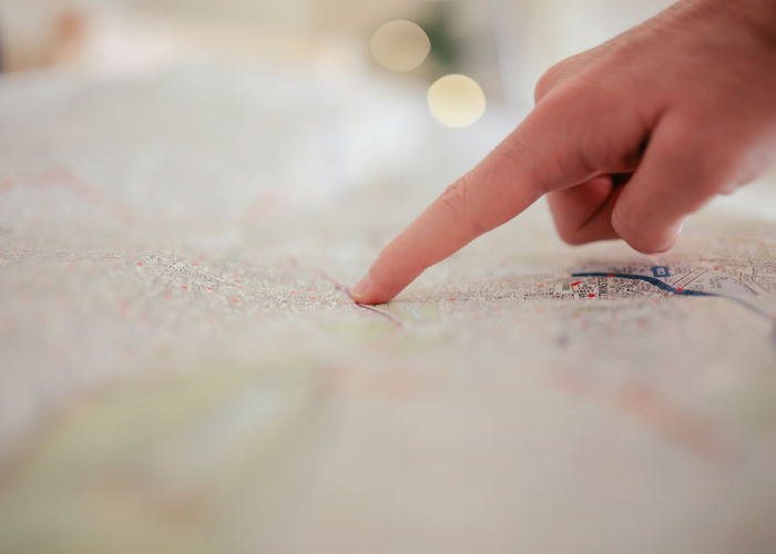 a person's finger pointing at a location on a map
