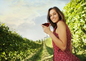 woman enjoying a glass of red wine in a vineyard
