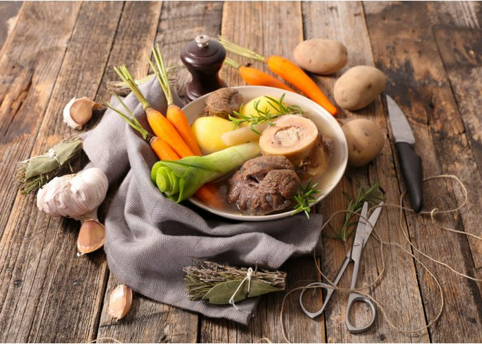 Ingredients for bone broth recipe in a bowl on a wooden table
