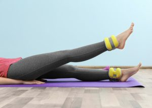 yellow ankle weights on a woman used for desk exercises in the office