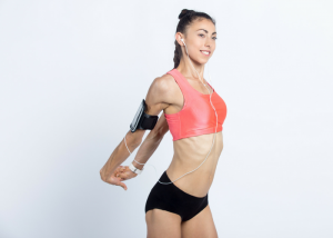 young female in sports wear doing chest stretch standing desk exercises