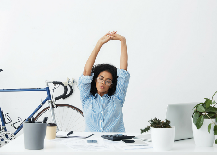 woman doing seated desk exercises stretching behind a large white office desk