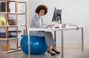 woman in a suit sitting on an exercise ball in her office