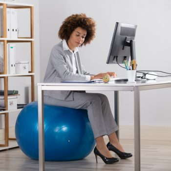 Woman in a suit sitting on an exercise ball at her desk in her office