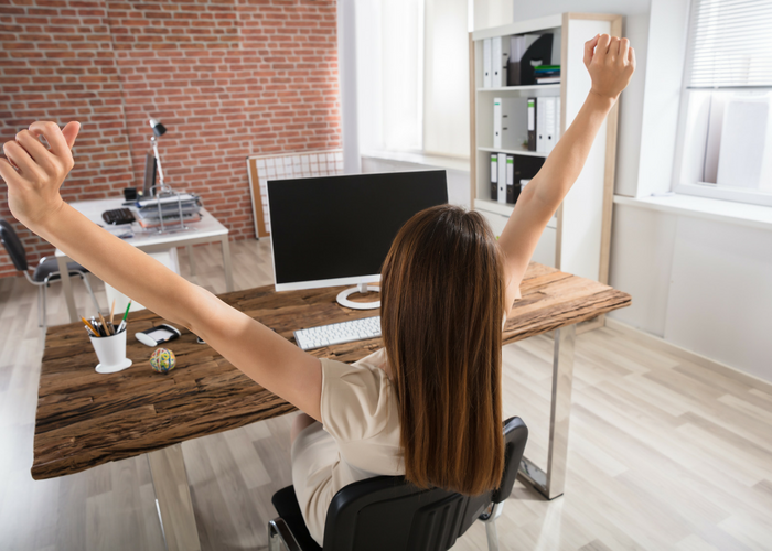 woman doing seated office exercises stretching behind a wooden desk