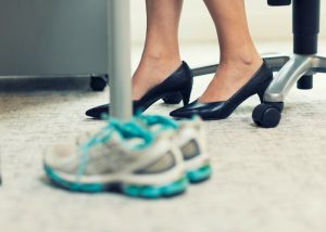 a professional woman seated at her desk in heels with running shoes set beside her