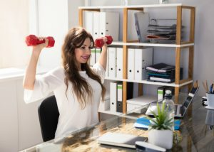 woman seated at a desk doing office exercises for arms with dumbbells