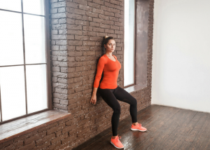 young woman in bright orange workout clothes doing wall sits