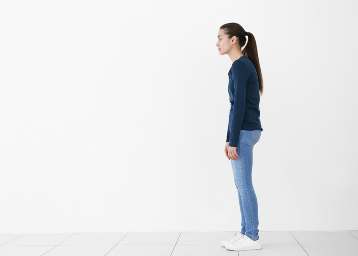 a girl standing upright with poor posture