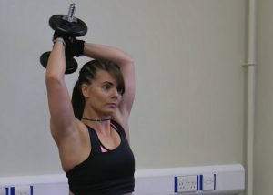 woman doing dumbbell halo exercises to improve posture