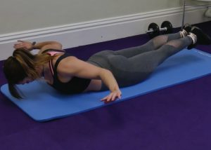 a woman face down on yoga mat with arms and legs lifted