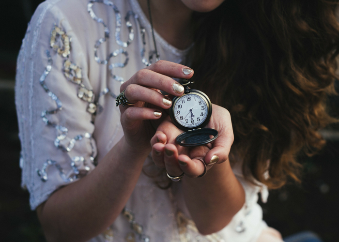 woman holding an antique pocket watch