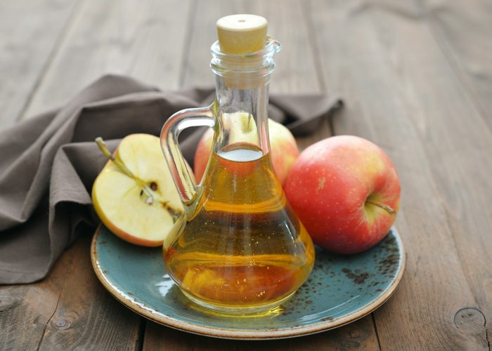 a bottle of apple cider vinegar and apples sitting on a blue dish