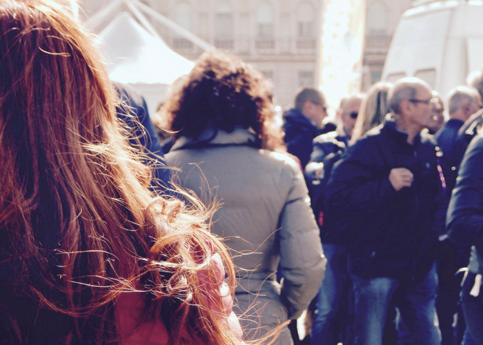 back of a woman's head in a crowd of people giving off human pheromones