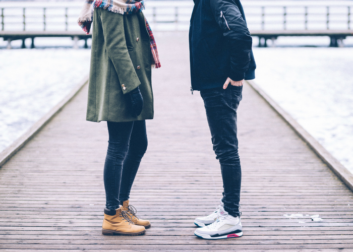 a man and woman standing on a dock facing each other